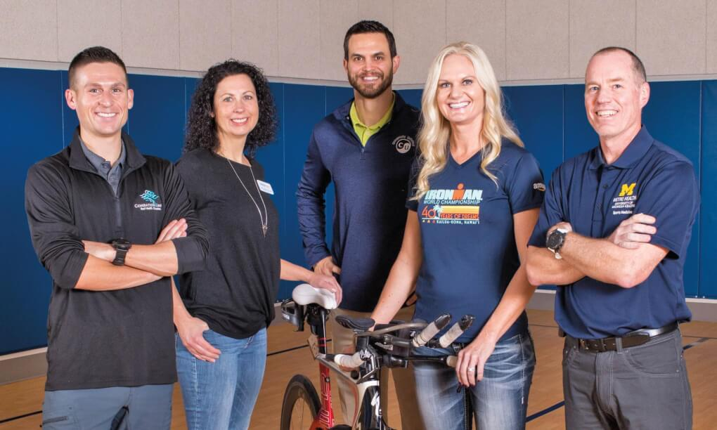 Woman with bike stands with team of people in a gym